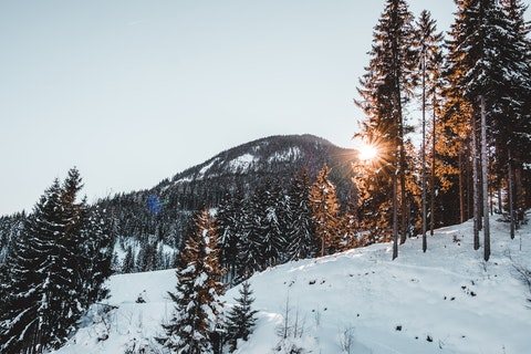 Solnedgång i snötäckta berg
